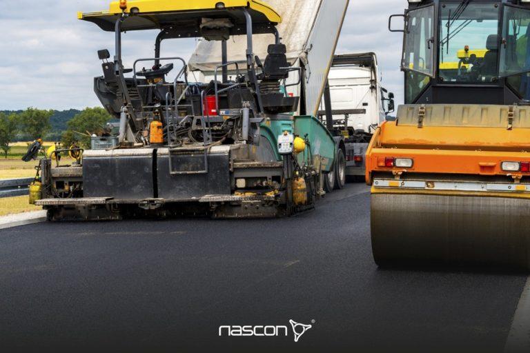 Prace nabudowie, czyli jak wykonuje się drogi asfaltowe. Rozściełacz doasfaltu iwalec wczasie układania warstwy asfaltowej.