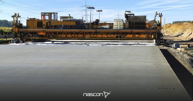 Drogi betonowe - budowa nawierzchni betonowej. Na drugim planie widoczny rozściełacz do betonu