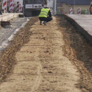 Przebudowa drogi DW966. Praca ztrudnym gruntem gliniastym. Woddali widoczny inżynier analizujący organoleptycznie grunt.