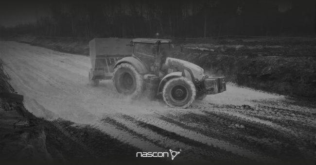 Osuszanie gruntu wapnem . Traktor z siewnikiem dozujący materiał osuszający.