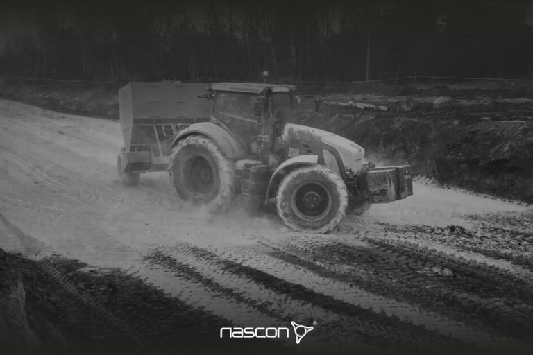 Osuszanie gruntu wapnem . Traktor zsiewnikiem dozujący materiał osuszający.